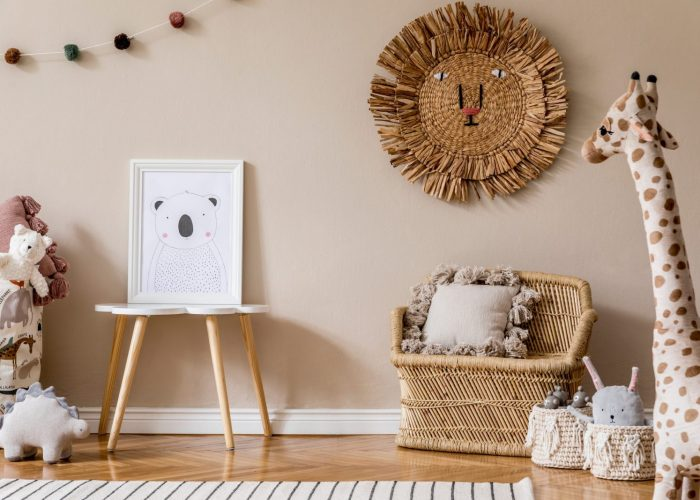 Stylish and modern scandinavian newborn baby interior with mock up photo frame on the small table. Toys, sofa with pillow and hanging cotton colorful balls. Beige wall. Design home staging. Template