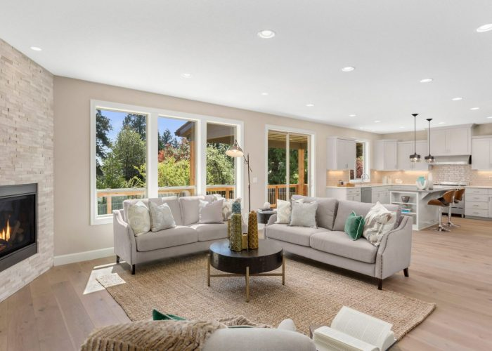 Beautiful living room in new home with open concept floor plan. Features large windows with abundant natural light, two couches and view of kitchen